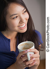 Smiling asian woman holding mug of coffee looking away