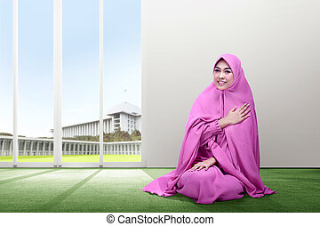 Smiling asian woman in pink veil sitting on carpet put her hand on chest and pray with all hearts inside the room