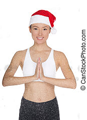 Smiling asian woman in Santa's hat engaged in fitness...