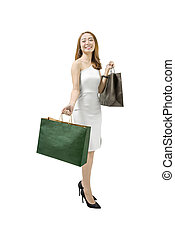 Smiling asian woman in white dress with shopping bags