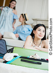 Smiling asian woman leaning on suitcase and thoughtfully looking away while friends packing clothes, packing luggage concept