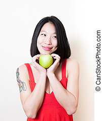 Smiling asian woman red dress with green apple on white