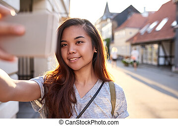 Smiling Asian woman taking a selfie in the city