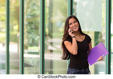 Smiling Asian woman talks on cell phone while walking next to glass building