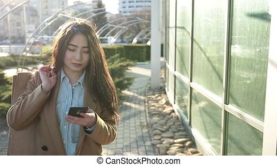 Smiling asian woman texting on smartphone outdoor