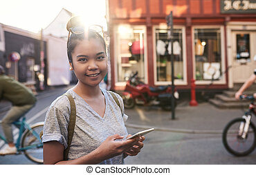 Smiling Asian woman walking in the city using her cellphone