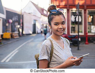 Smiling Asian woman with her cellphone standing in the city