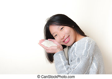 Smiling asian woman with rice in hands. Feed the world concept