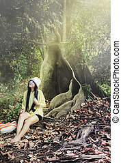 Smiling Asian women in relax summer dress sitting under big tree bush in green forest