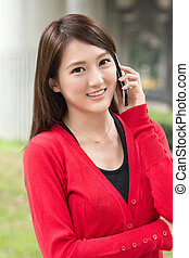 Smiling Asian young woman take a call
