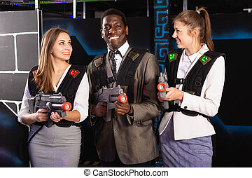Smiling associates - afro man and two European women posing at laser tag room