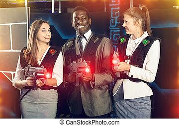 Smiling associates - afro man and two European women posing at