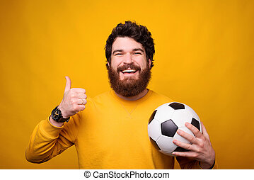 Smiling at the camera man is showing thumb up and holding a soccer ball.