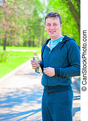 smiling athlete with bottle of water outdoors