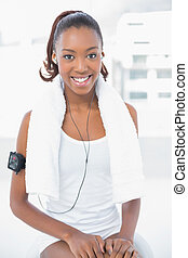 Smiling athletic woman listening to music