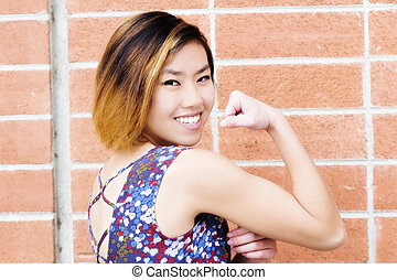Smiling Attractive Asian American Woman Showing Biceps