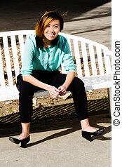 Smiling Attractive Asian American Woman Sitting On Bench