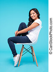Smiling attractive asian woman sitting on the chair