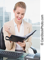 Smiling attractive businesswoman holding her agenda