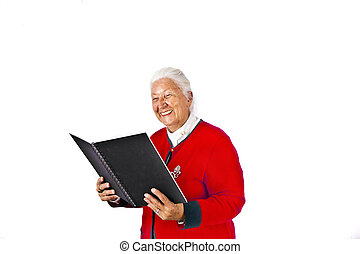 smiling attractive elderly woman reading in a book and...