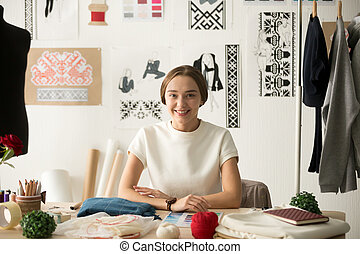 Smiling attractive fashion designer sitting at workplace looking
