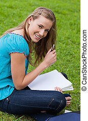 Smiling attractive girl holding her pen while looking straight at the camera