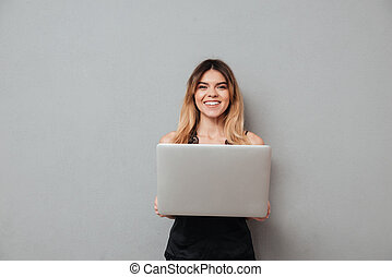 Smiling attractive girl holding laptop computer and looking at camera