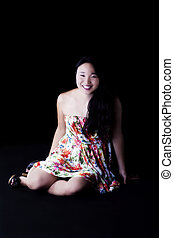Smiling Attractive Japanese American Woman Sitting In Dress