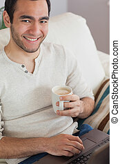 Smiling attractive man drinking