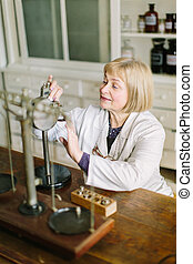Smiling attractive middle-aged blond lady pharmacist holding her hands on the vintage refractometer in the laboratory room in pharmacy