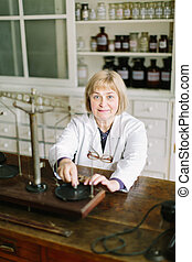 Smiling attractive middle-aged blond lady pharmacist working with vintage scales in the pharmacy