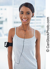 Smiling attractive model in sportswear listening to music