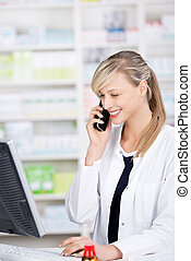 Smiling attractive pharmacist talking at the phone