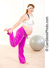 Smiling attractive pregnant woman making gymnastics  at home
