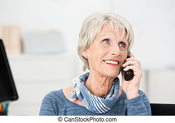 Smiling attractive senior women using a mobile phone looking...