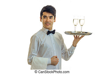 smiling attractive waiter is straight and raised in hand a tray with glasses of wine close-up isolated on white background