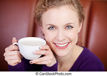 smiling attractive woman enjoying cup of coffee