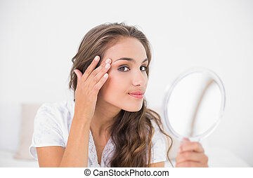 Smiling attractive woman holding mirror