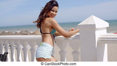 Smiling attractive woman in a sexy summer outfit standing...