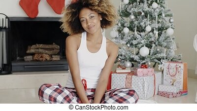 Smiling attractive woman in front of the Xmas tree