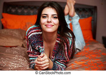 Smiling attractive woman lying on the bed at home