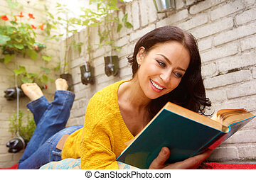 Smiling attractive woman reading book