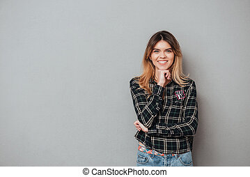 Smiling attractive woman standing and holding hand at her chin