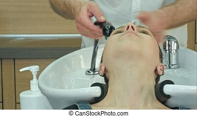 Smiling attractive woman with her eyes closed in enjoyment having a hair shampoo at the hair salon