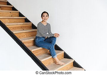 Smiling attractive young asian woman sitting on a staircase
