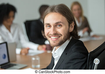 Smiling attractive young businessman in suit looking at camera,