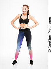 Smiling attractive young fitness woman in sportwear standing...