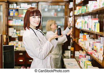 Smiling attractive young lady pharmacist holding a bottle of medicines in her hand with focus to her face. Other woman pharmacist choosing the drug on the background