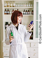 Smiling attractive young lady pharmacist holding green and blue glass bottles in her hands on the background of pharmacy interior