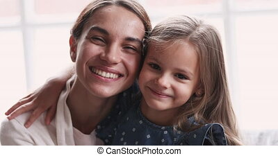 Smiling attractive young mixed race mom bonding with cute daughter.
